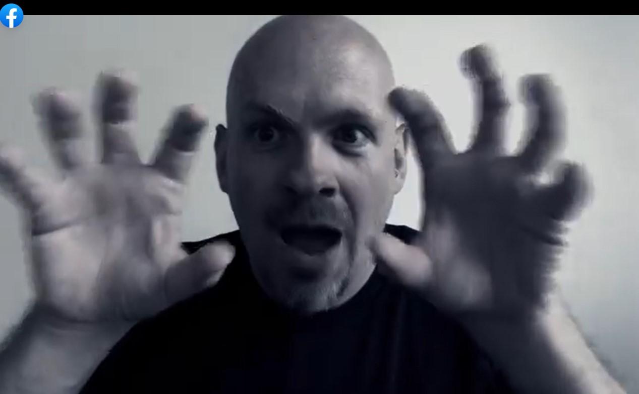 Kuvassa mieshenkilön kasvokuva, silmät suurina ja suu ammollaan, kädet kasvojen sivuilla sormet erillään.